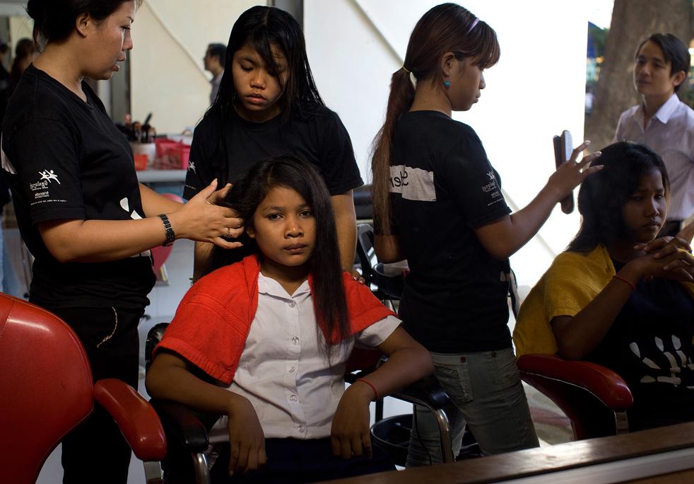 21. Студентка образовательного центра «Международные друзья» учится парикмахерскому искусству в салоне красоты в Пномпене 5 февраля. «Международные друзья» и их партнер «Мит Замлат» - неправительственные организации, работающие с ограниченной молодежью, уличными детьми, наркоманами и жертвами СПИДа. Они предоставляют им доступ к образованию и различным секциям. (Getty Images / Paula Bronstein)