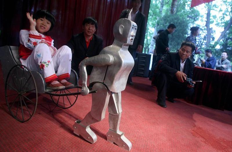 """22. Ву Юлу, китайский фермер, создающий роботов, показывает одну из своих работ в парке в Пекине. Ву, хорошо известный в Китае своими проектами, не использует ничего, кроме """"лома и пяти классов образования"""". (фото: Getty Images)"""