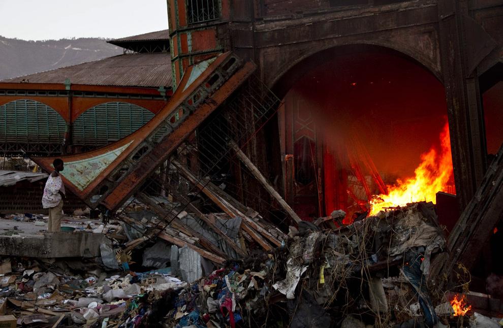 3. Мальчик смотрит, как огонь разгорается на Айрон Маркет в Порт-о-Пренс 29 января 2010 года. (JODY AMIET/AFP/Getty Images)