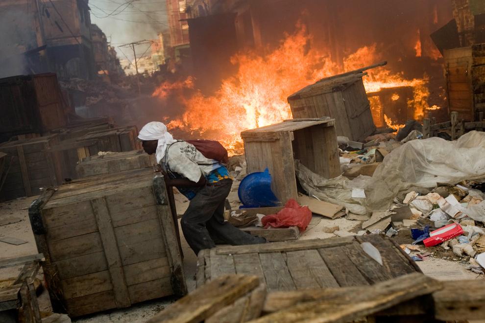 4. Мужчина отодвигает ящики от пожара, поглотившего магазины на рыночной площади 29 января 2010 года в центре Порт-о-Пренс. (Marco Dormino/MINUSTAH via Getty Images)