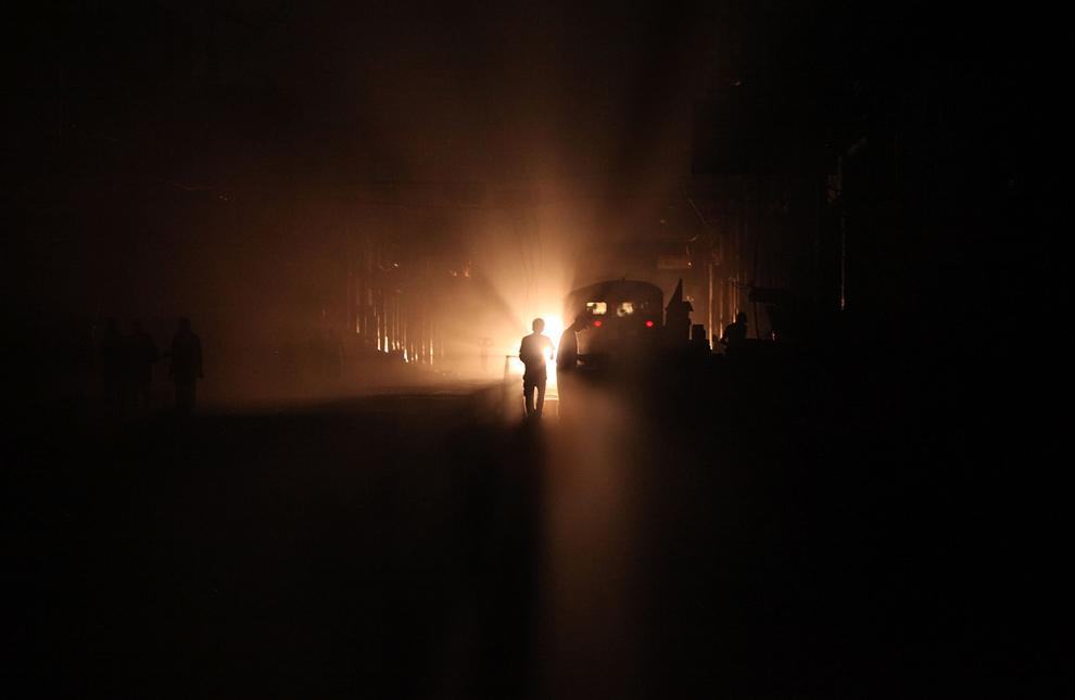 6. Силуэт человека на фоне света от фар на темной улице, где по-прежнему нет электричества, 31 января 2010 года в Порт-о-Пренс. (Mario Tama/Getty Images)