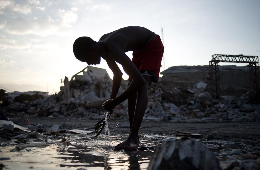 7. Парень умывается прямо на улице в Порт-о-Пренс 31 января 2010 года. (FRED DUFOUR/AFP/Getty Images)