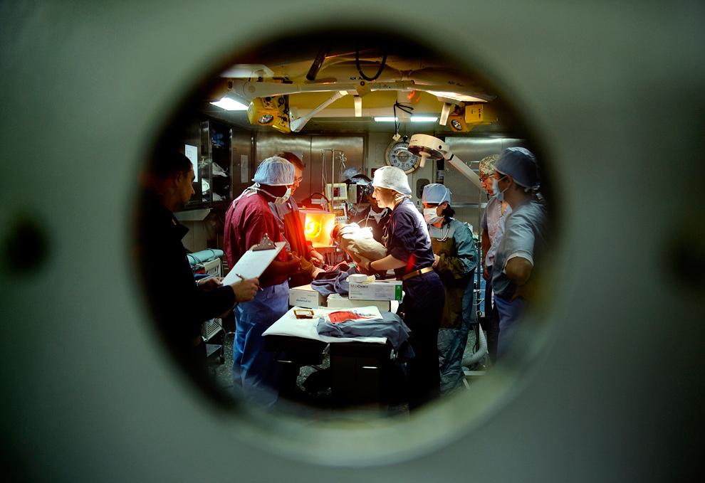 9. Лейтенант Натали Шафер (в центре), являющаяся медсестрой на борту десантного вертолётоносца «Батан» в Байе Де Гранд Гоав, Гаити, передает новорожденного мальчика отцу 30 января 2010 года. Это первый ребенок, родившийся на борту «Батана», поддерживающего операцию единой реакции в Гаити 12 января 2010 года. (REUTERS/U.S. Navy/Kristopher Wilson)