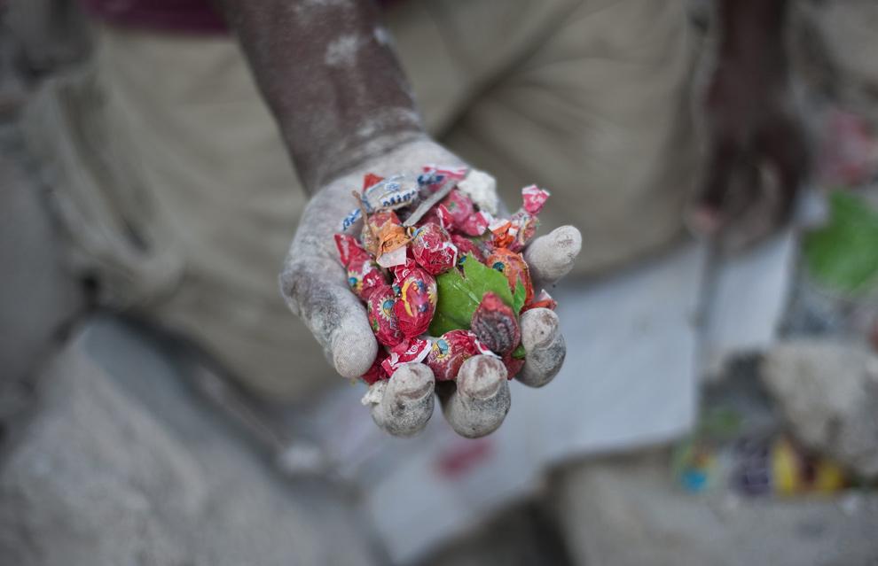 10. Мальчик показывает конфеты, которые он нашел в разрушенном здании в Порт-о-Пренс 27 января 2010 года. (FRED DUFOUR/AFP/Getty Images)