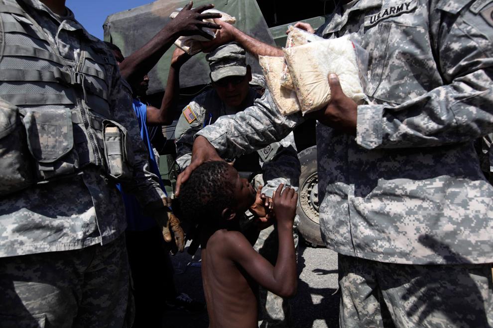 12. Ребенок просит у солдата еду во время операции по раздаче продуктов питания в трущобах Сайт-Солейл 30 января 2010 года. (AP Photo/Ramon Espinosa)