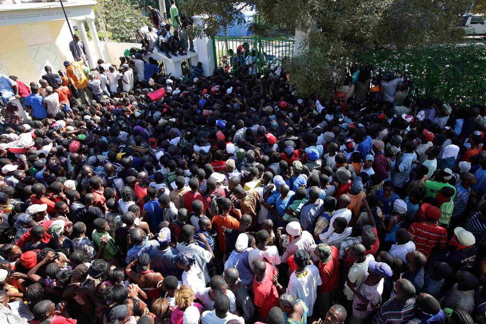 13. Люди пытаются пробиться через толпу, ожидающую раздачи еды, в Порт-о-Пренс 28 января 2010 года. Многим жертвам землетрясения по-прежнему не хватает еды, так как центрам по раздаче продуктов часто не хватает координации и защиты. (AP Photo/Gregory Bull)