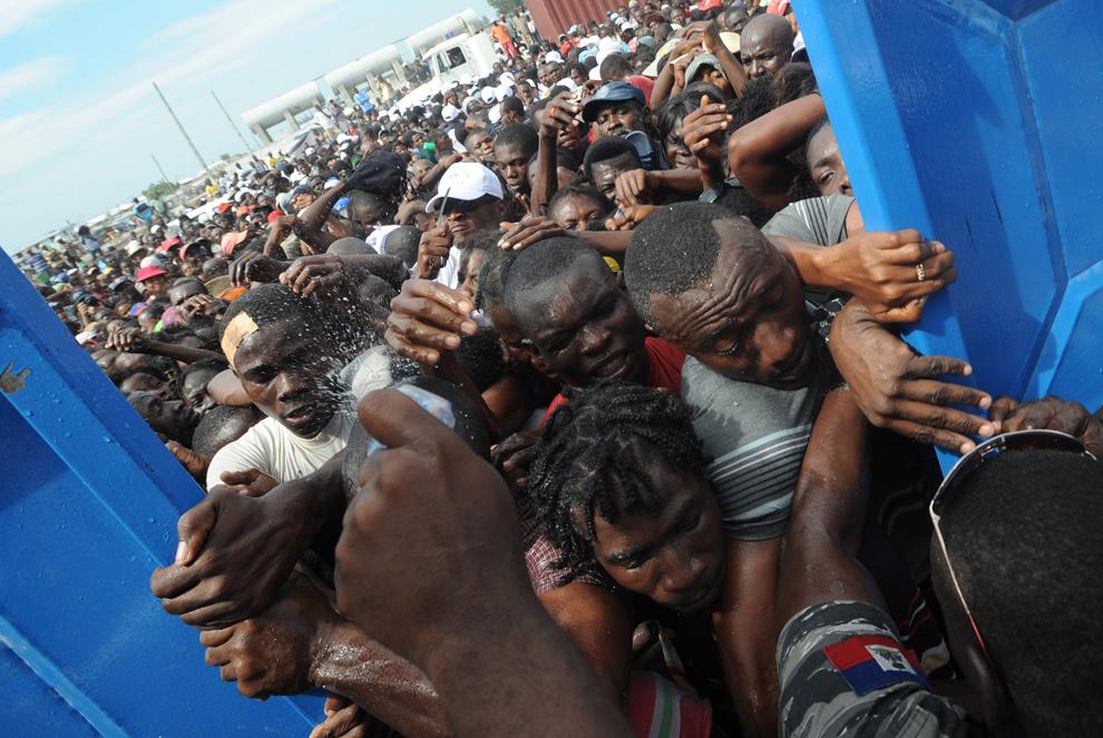 14. Жители Сайт Солейл отчаянно пытаются войти в полицейский участок, где располагается центр раздачи еды, в Порт-о-Пренс 26 января 2010 года. (THONY BELIZAIRE/AFP/Getty Images)