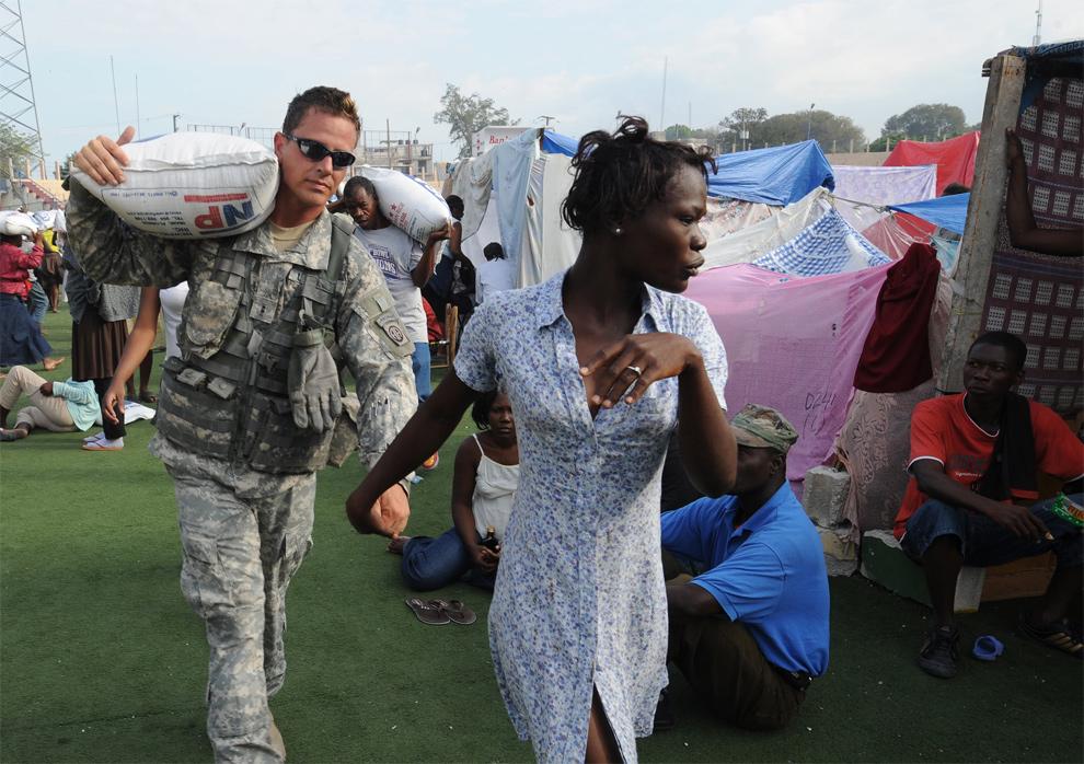 15. Парашютист из 82-ой воздушной дивизии несет мешок с рисом для женщины, которая ни на минуту не выпускает его руку, в центре раздачи еды в Порт-о-Пренс 31 января 2010 года. (THONY BELIZAIRE/AFP/Getty Images)