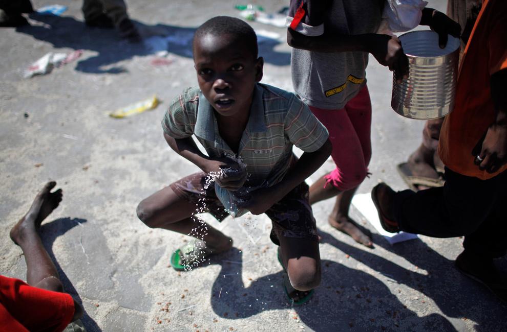 16. Мальчик пытается унести рис и бобы в рубашке в центре раздачи еды в Сайт Солейл, Порт-о-Пренс, 28 января 2010 года. (REUTERS/Carlos Barria)