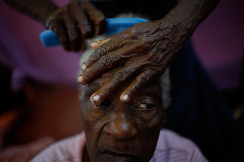 20. 80-летнюю Андре Джин причесывает сестра 70-летняя Лежерик Харлес в муниципальном доме престарелых в Порт-о-Пренс 27 января 2010 года. Частные спонсоры и директор дома регулярно приносят еду, но пациенты снаружи говорят, что они хотят есть с самого момента землетрясения 12 января. (AP Photo/Rodrigo Abd)