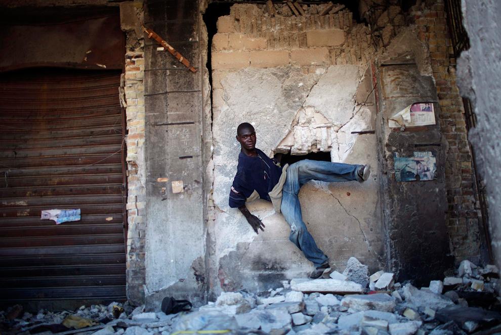 21. Мародер покидает разрушенное здание через дыру в стене в центре Порт-о-Пренс 29 января 2010 года. (REUTERS/Carlos Barria)