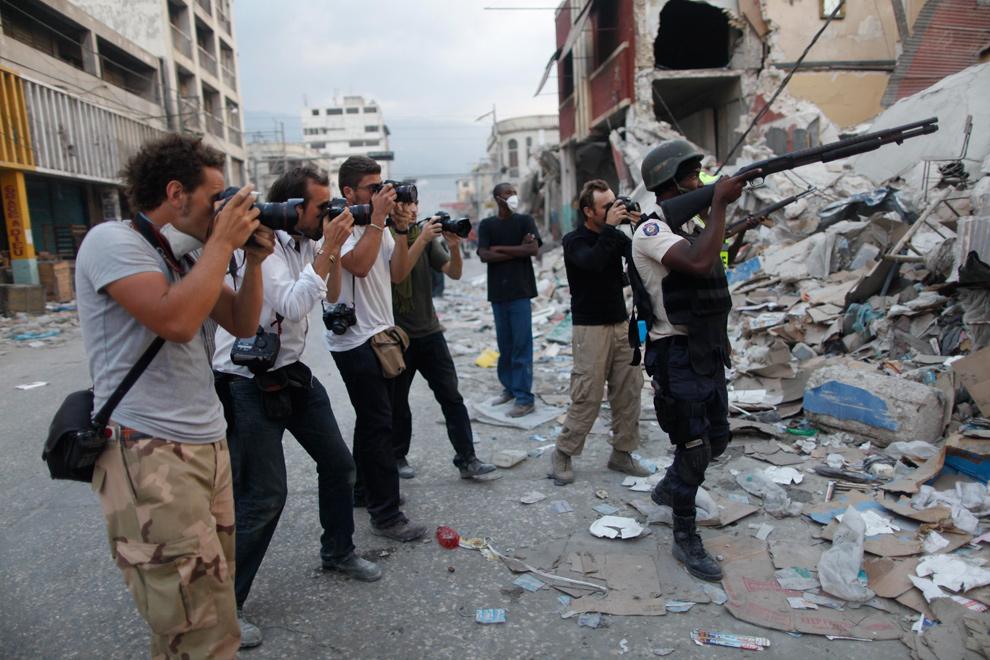 22. Фотожурналисты окружили гаитянского полицейского, нацелившегося на мародера, в центре Порт-о-Пренс 26 января 2010 года. (AP Photo/Rodrigo Abd)