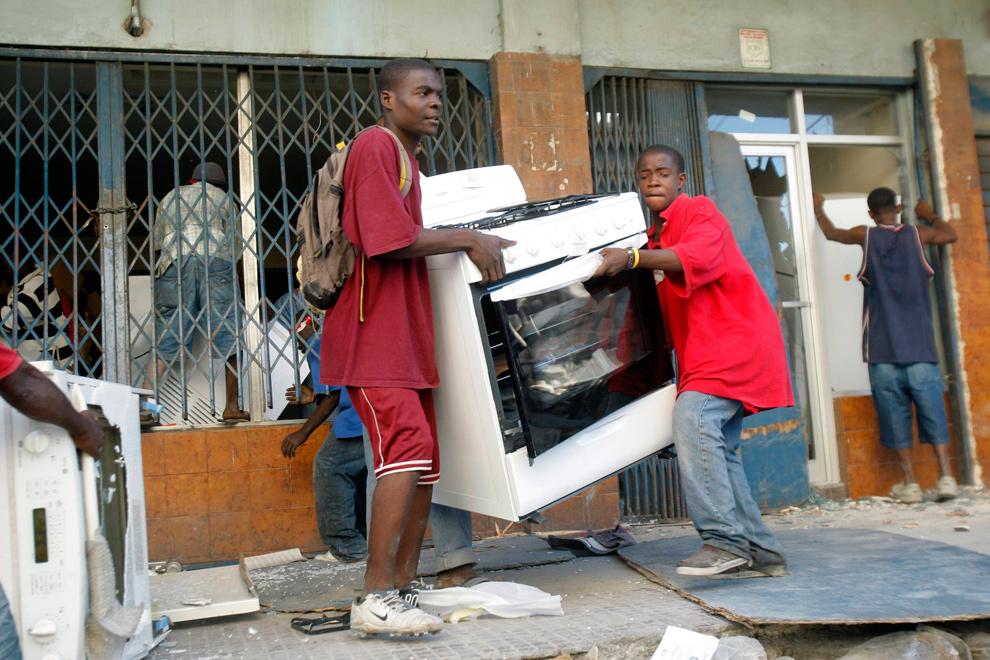 23. Люди уносят плиту из магазина бытовой техники до приезда гаитянской полиции в центре Порт-о-Пренс 29 января 2010 года. (REUTERS/St Felix Evens)