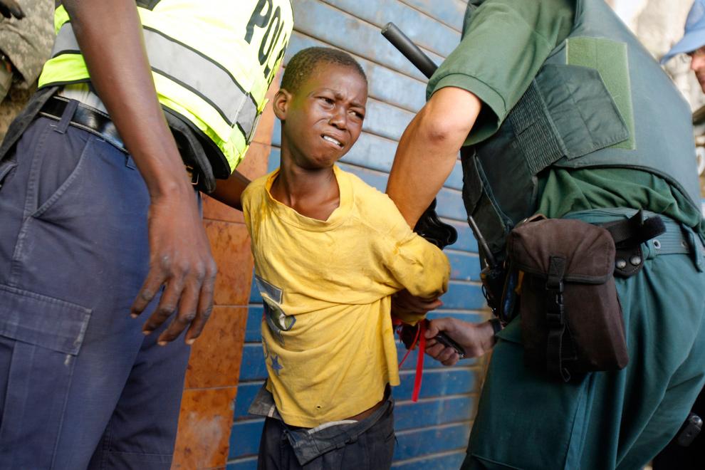 24. Полицейский ООН развязывает руки мальчика, принимавшего участие в мародерстве в центре Порт-о-Пренс 29 января 2010 года. (REUTERS/St Felix Evens)