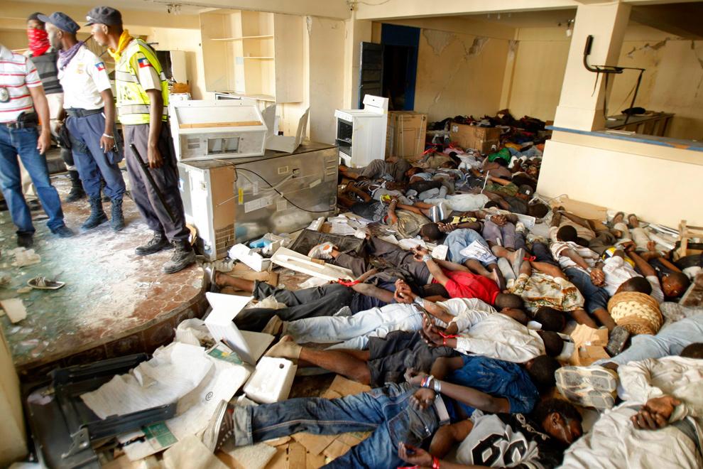 25. Гаитянские полицейские охраняют 45 арестованных, связанных и лежащих на полу, которых обвиняют в мародерстве, в центре Порт-о-Пренс 29 января 2010 года. (REUTERS/St Felix Evens)