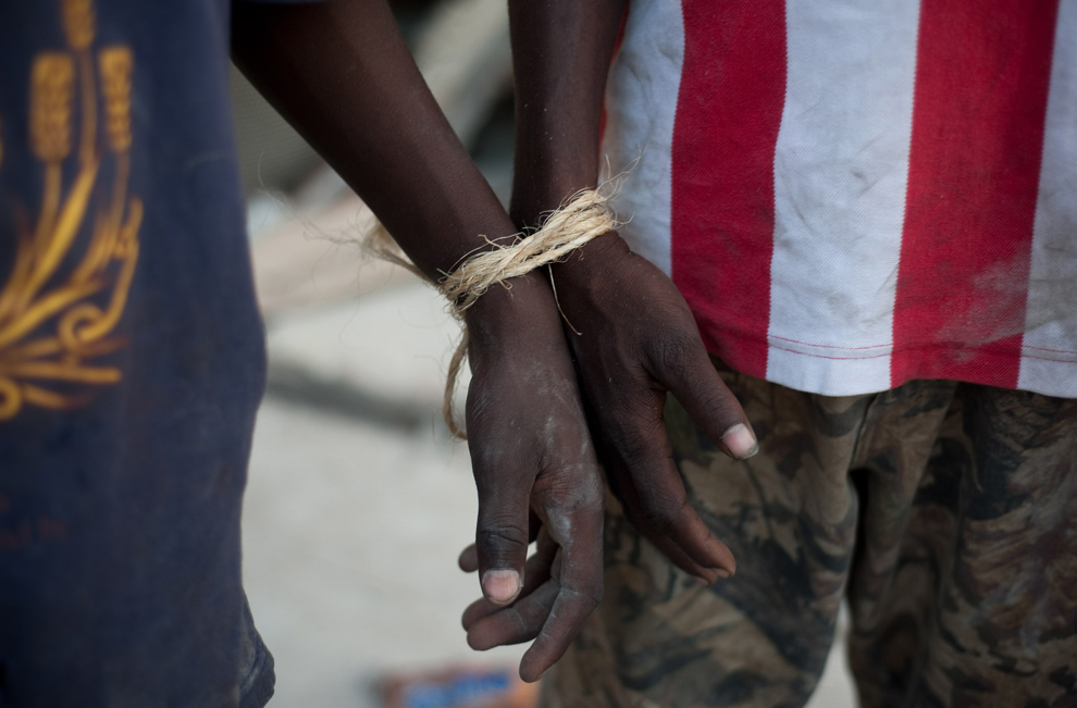 26. Два мародера связаны вместе в Порт-о-Пренс 30 января 2010 года. (FRED DUFOUR/AFP/Getty Images)