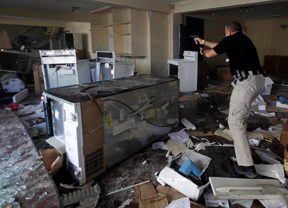 27. Частный охранник стреляет в мародера на лестнице (вверху слева) в доме в центре Порт-о-Пренс 29 января 2010 года. (AP Photo/Ramon Espinosa)