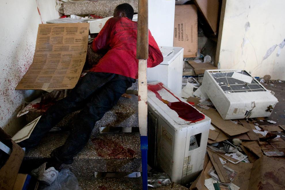 28. Мертвый мародер лежит на лестнице, подстреленный частным охранником в доме в Порт-о-Пренс 29 января 2010 года. (Marco Dormino/MINUSTAH via Getty Images)