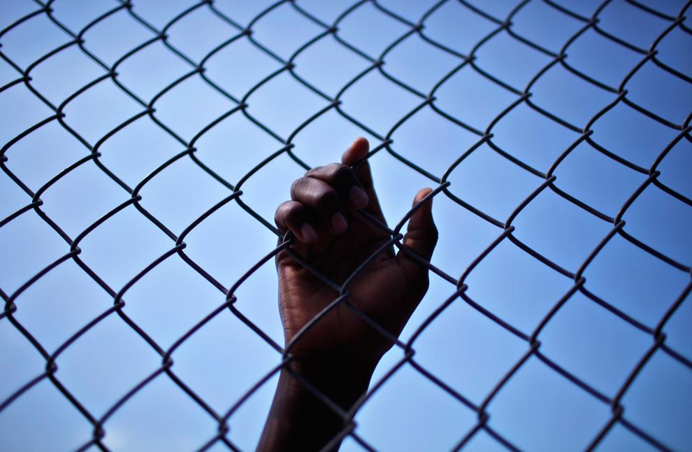 29. Человек положил руку на забор во время раздачи еды в Порт-о-Пренс 30 января 2010 года. (REUTERS/Carlos Barria)