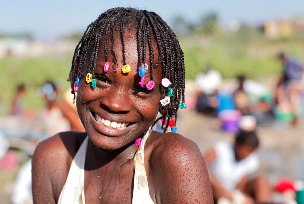 37. Девочка улыбается, набирая воду, в Сайт-Солейл в Порт-о-Пресн 27 января 2010 года. (REUTERS/Eduardo Munoz)