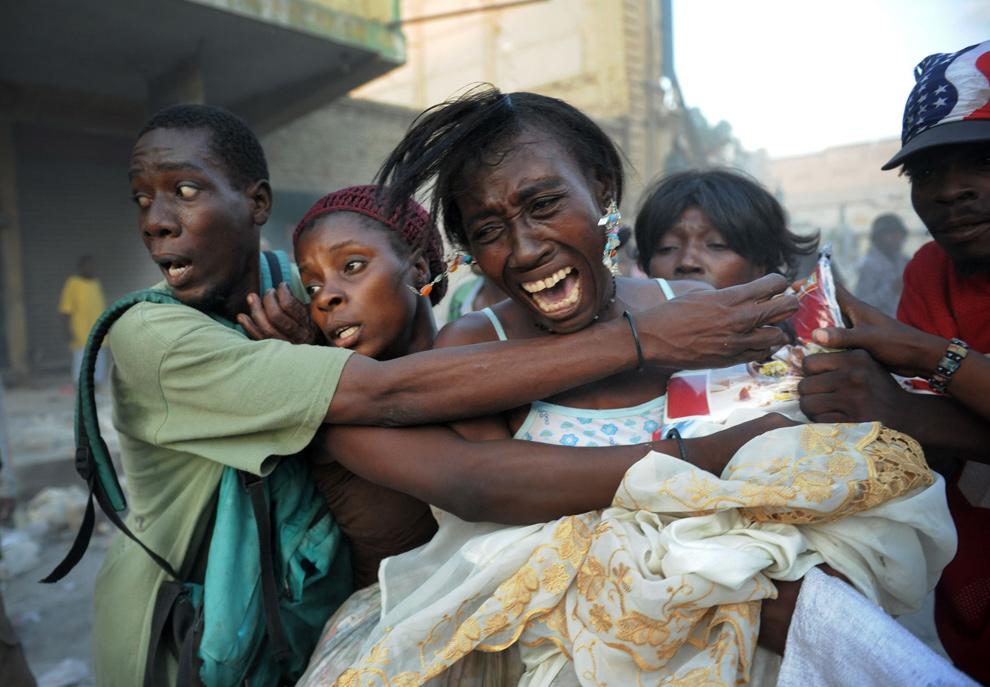 38. Торговка пытается спасти свои товары от толпы в Порт-о-Пренс 24 января 2010 года. (ROBERTO SCHMIDT/AFP/Getty Images)