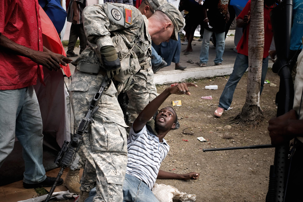 39. Парашютист из 82-ой воздушной дивизии держит человека, пытавшегося пробиться без очереди во время раздачи еды в Порт-о-Пренс 31 января 2010 года. (JEAN-PHILIPPE KSIAZEK/AFP/Getty Images)
