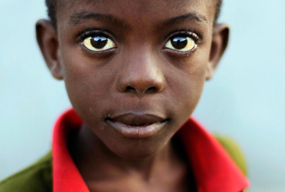 40. Мальчик смотрит в камеру во время воскресной службы у лагеря для бездомных в Порт-о-Пренс 24 января 2010 года. (REUTERS/Tomas Bravo)