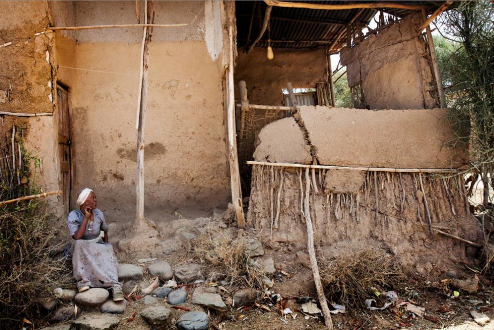 13. Женщина сидит у своего обветшалого глинобитного дома. (Agton Strom)
