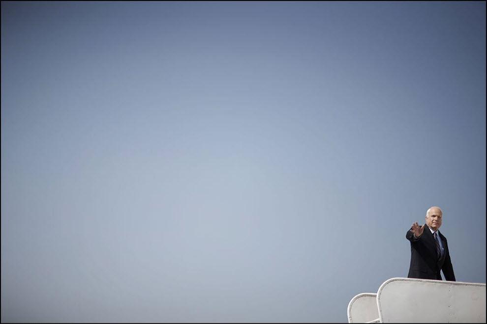 23) Джон Маккейн садится в самолёт.