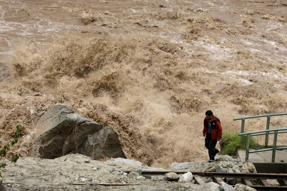 2. Мужчина идет рядом с поврежденными рельсовыми путями рядом с рекой Урубамба в Мачу-Пикчу Пуэбло в Куско, Перу, 28 января. (AP / Martin Mejia)