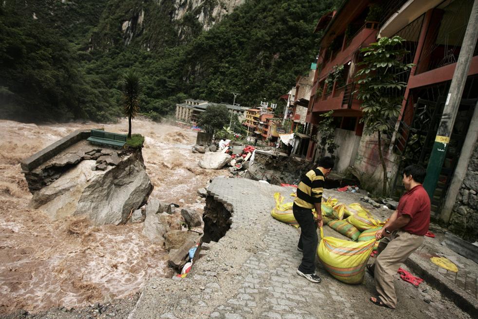 4. Иностранные туристы помогают сделать дамбу, чтобы сдержать воды реки Вилканота в Агуас Калиентес, недалеко от археологического места Мачу-Пикчу Пуэбло 28 января. (AFP / Getty Images)