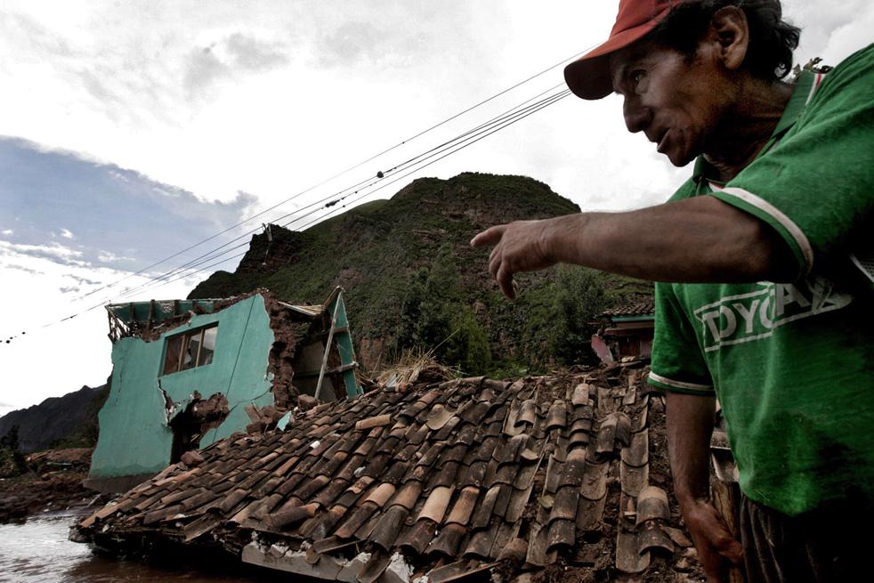 5. Мужчина указывает на дом, который был уничтожен в результате наводнения реки Вилканота в деревне Урубамба, недалеко от Мачу-Пикчу в Куско 28 января. (AFP / Getty Images)