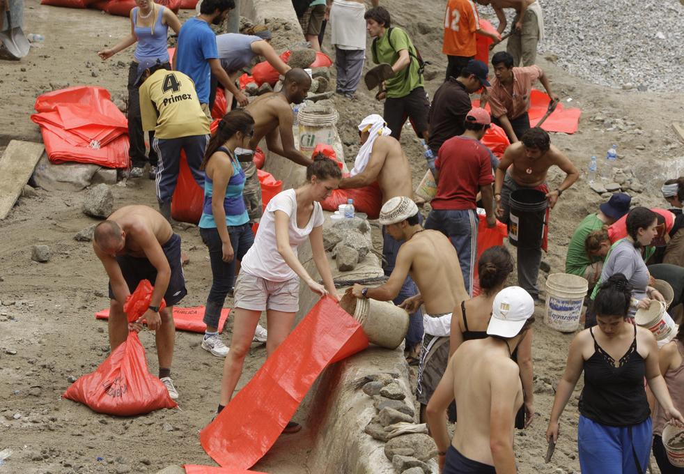 6. Иностранные туристы помогают наполнять мешки песком, чтобы попытаться сдержать воду, рядом с рекой Урубамба в Мачу-Пикчу Пуэбло в Куско 28 января. (AP / Martin Mejia)