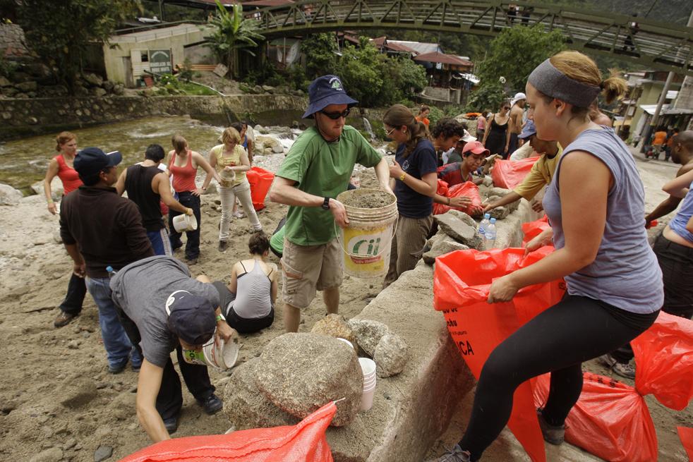 7. Иностранные туристы помогают наполнять мешки песком, чтобы попытаться сдержать воду, рядом с рекой Урубамба в Мачу-Пикчу Пуэбло в Куско 28 января. (AP / Martin Mejia)