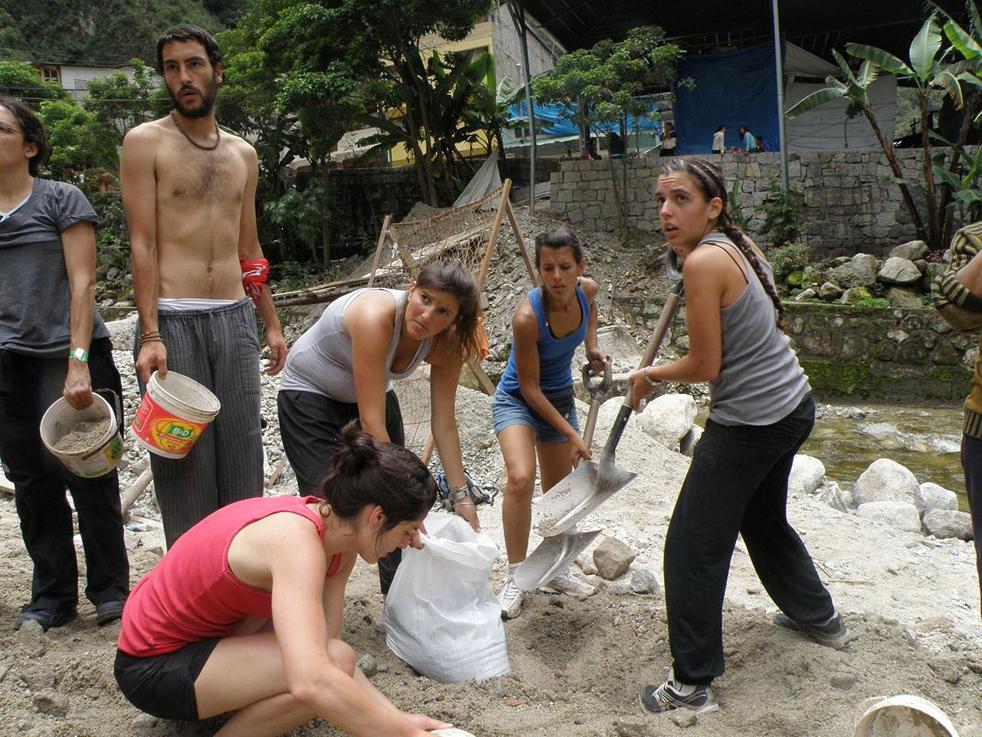 8. Иностранные туристы помогают наполнить мешки песком, чтобы попытаться сдержать воды реки Вилканота в Куско, недалеко от Мачу-Пикчу Пуэбло 28 января. (AFP / Getty Images)