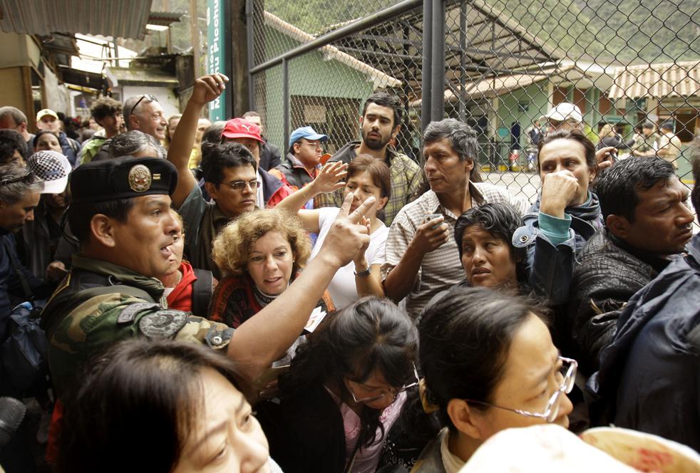 10. Перуанские солдаты сдерживают иностранных туристов, пытающихся эвакуироваться из Мачу-Пикчу Пуэбло в городе Куско 28 января. (AP / Martin Mejia)