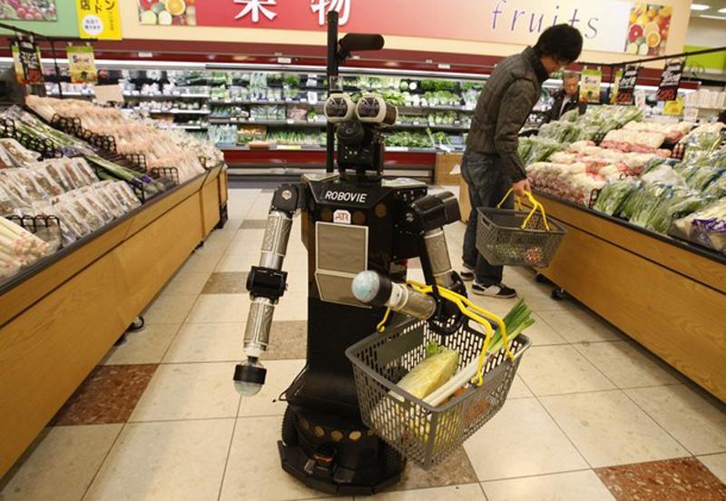 """13. Робот по имени """"Robovie-II"""", разработанный японским исследовательским институтом робототехники ATR, встречает покупателя у входа в магазин, следует за ним к продуктовым полкам, удерживая корзины, и напоминает ему по пунктам список покупок. (фото: Reuters)"""