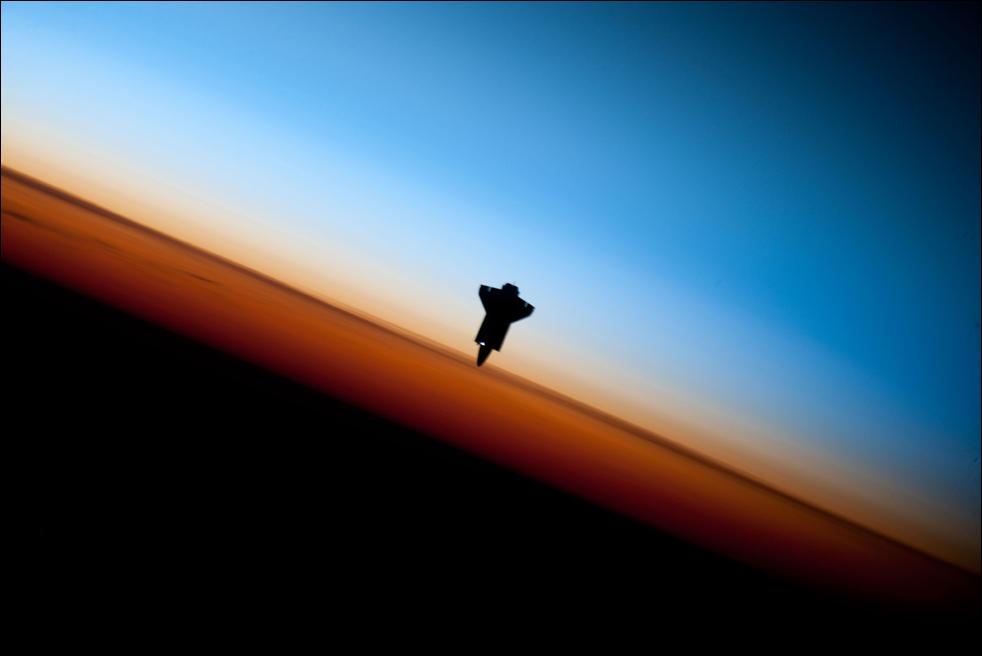 1. Силуэт шаттла «Endeavour» над красочным горизонтом Земли. Фото сделано членом экипажа «Экспедиции 22» перед операцией по стыковке с Международной космической станцией 9 февраля. (AP / NASA)