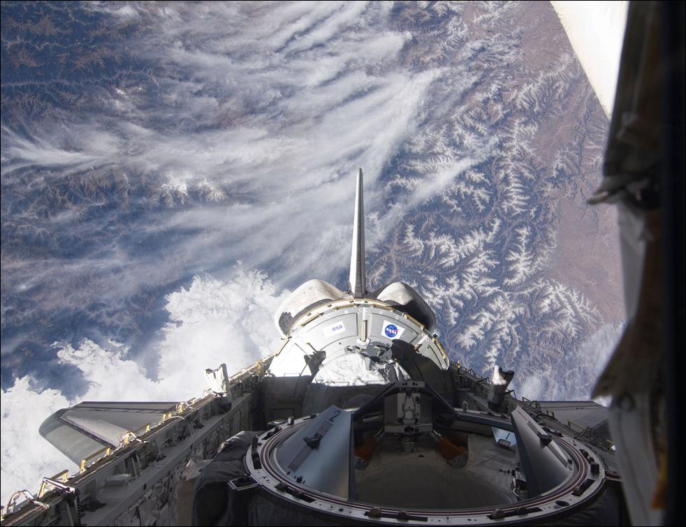 14. Узел «Tranquility» на грузовом отсеке корабля«Endeavour», вертикальный стабилизатор, линза системы орбитального маневрирования и механизм состыковки на фоне горного пейзажа Земли 9 февраля. (AP / NASA)