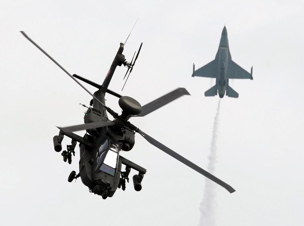 8. Истребитель ВВС республики Сингапур и вертолет AH-64 пролетают мимо друг друга во время выступления для прессы на авиасалоне в Сингапуре 31 января. (AFP / Getty Images / Roslan Rahman)