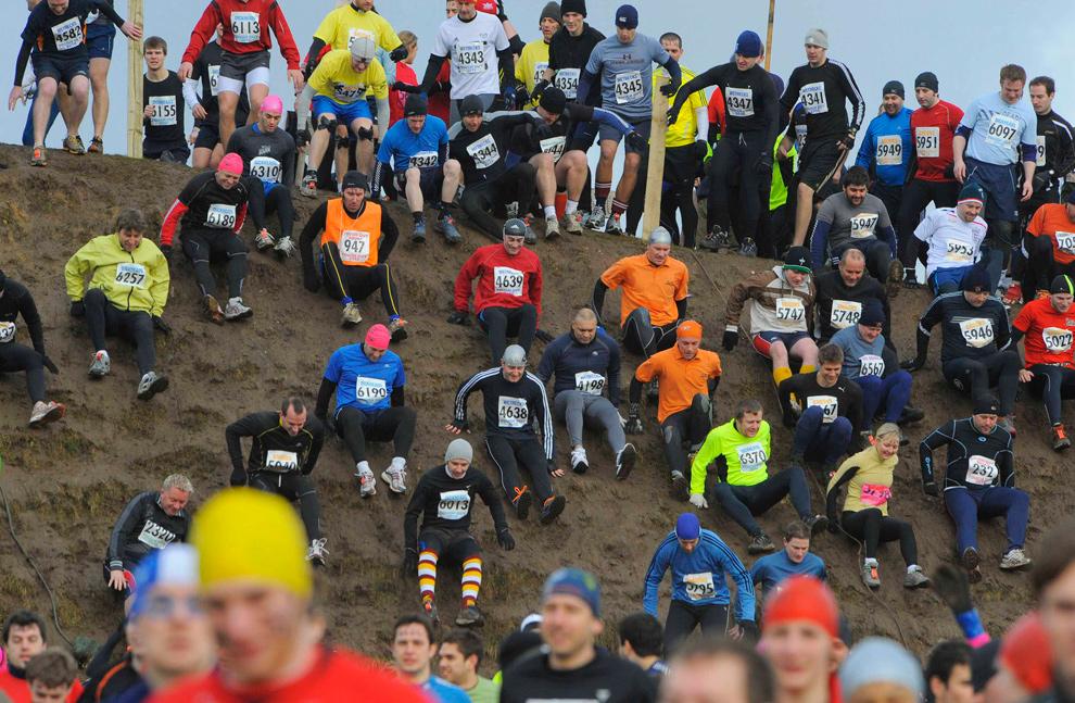 2. Мужчины и женщины катятся вниз по склону холма на старте гонки «Tough Guy» в Волверхэмптоне 31 января. (REUTERS/Nigel Roddis)