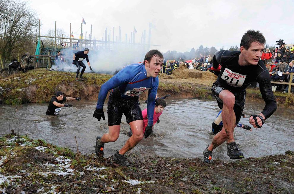 7. Участники соревнования выбегают из грязной лужи, спеша к следующему препятствию. (REUTERS/Nigel Roddis)