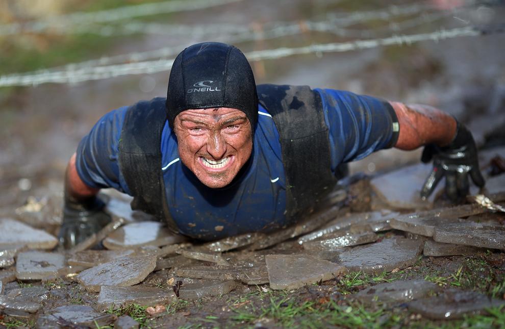 8. Участник «Tough Guy» ползет по грязи под колючей проволокой 31 января 2010 года. (AP Photo/Simon Dawson)