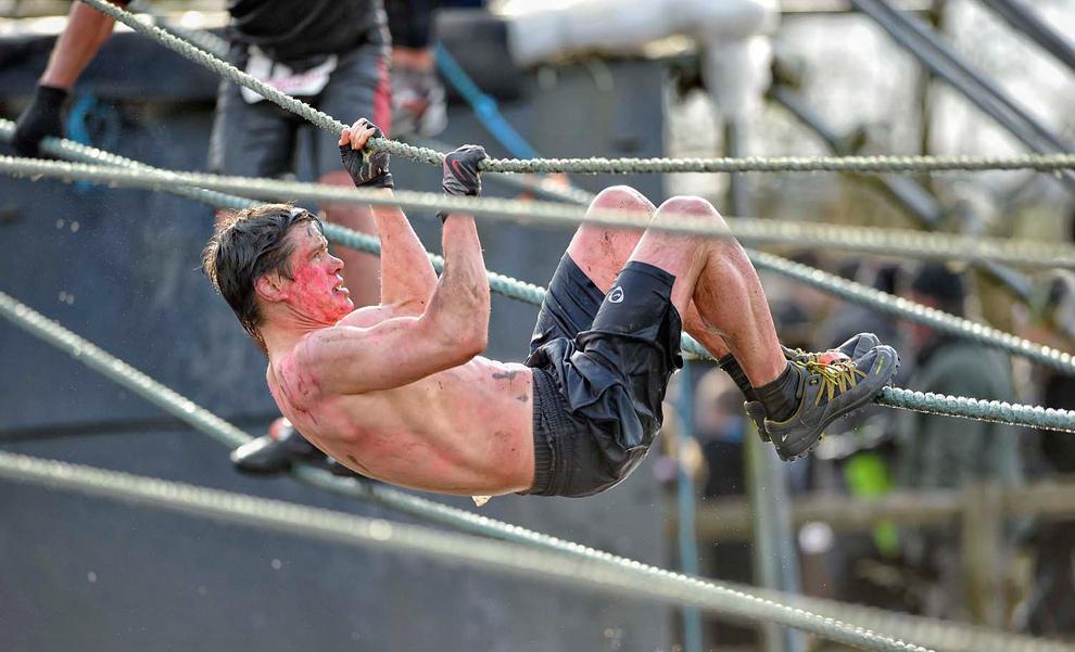 12. Участник соревнования весь в грязи, воде и краске пробирается по веревочному мосту. (© Mike King)