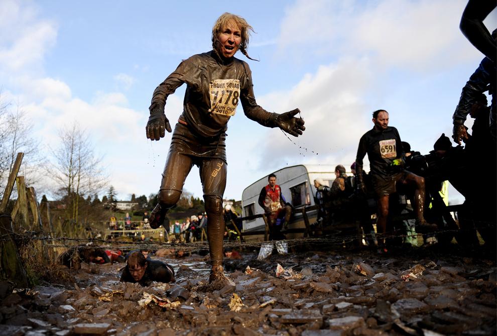 13. Девушка-участница соревнования «Tough Guy» преодолела препятствие с колючей проволокой 31 января 2010 года. (Michael Regan/Getty Images)