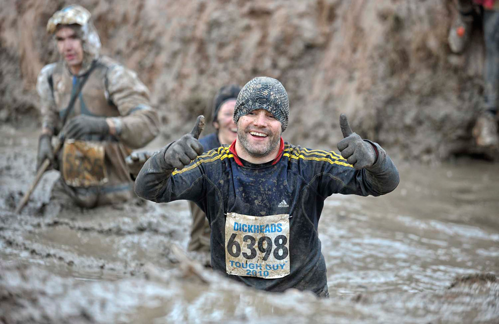 27. Грязный, но счастливый участник соревнования «Tough Guy» поднимает вверх большие пальцы, пробираясь по грязи 31 января 2010 года. (© Mike King)