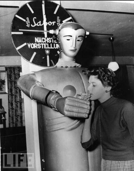 6. Сабот рыцарски предлагает подкурить сигарету молодой женщине в универмаге в Мюнхене. (фото: Keystone / Getty Images) 1955