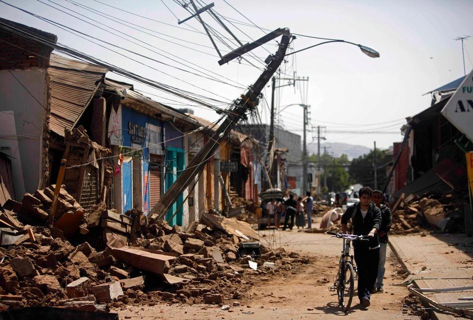 13. Жители Тальки идут по разрушенной землетрясением улице. (AP Photo/Roberto Candia)
