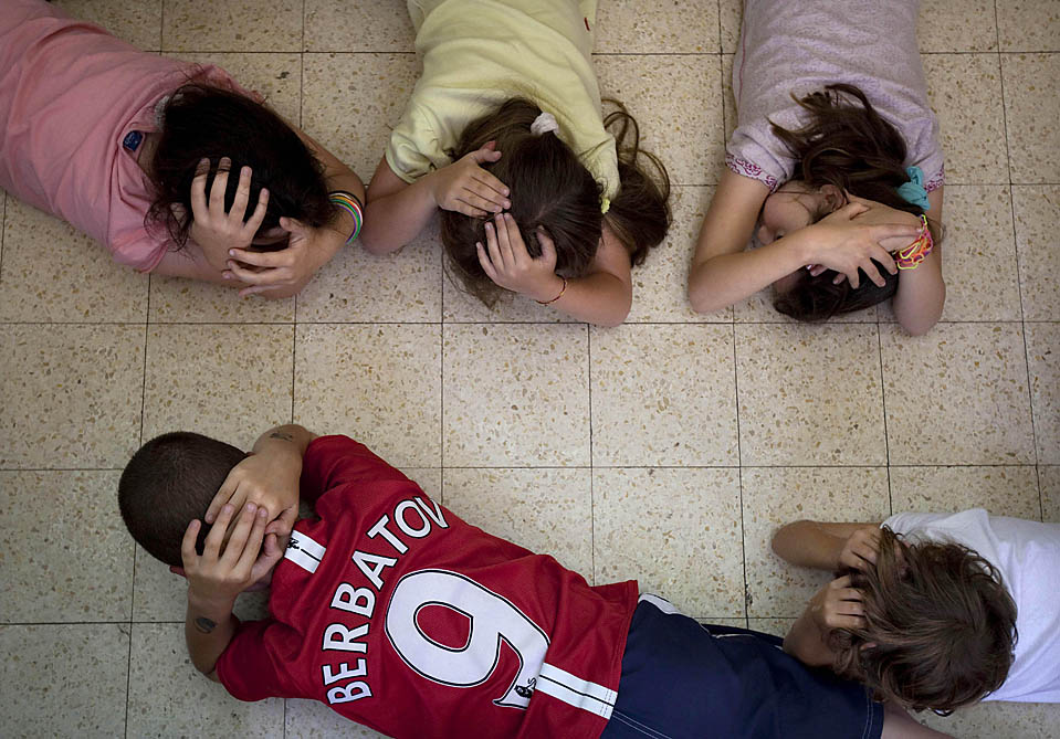 2. Израильские дети прикрываются в классе во время учений в Тель-Авиве. Взрослые также бросились в укрытия. Израиль практикует ответ на ракетные атаки. (Oded Balilty/Associated Press)