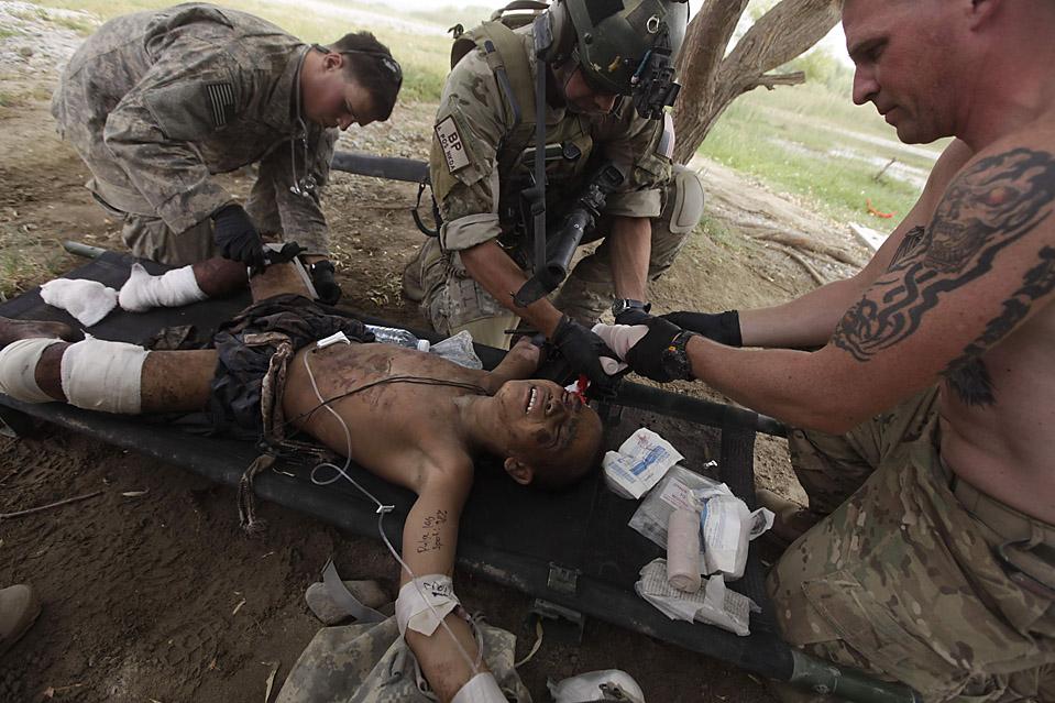 4. Сержант ВВС Бренден Паттерсон (в центре) и два американских солдата оказывают помощь афганскому мальчику, наступившему на самодельную мину. В результате мальчику оторвало руку, он также получил серьезные травмы ног. (Brennan Linsley/Associated Press)